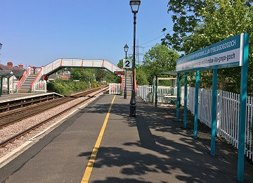 Station name and footbridge at Llanfairpwll railway station