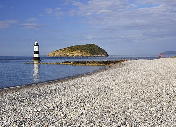 The stony beach at Penmon Point with Puffin Island and Trwyn Du lighthouse