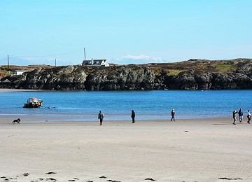 Rhoscolyn beach with people enjoying the view