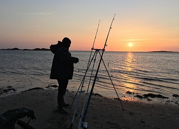 Shore fishing at Rhosneigr on Anglesey as the sun sets