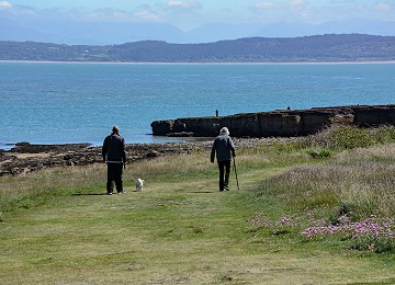 Walking along the headland in summer at Moelfre